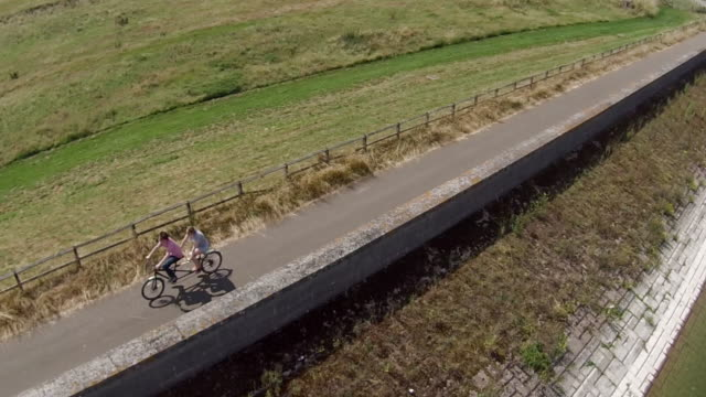 two people on a tandem bike ride over an aquaduct - tandem stock videos & royalty-free footage