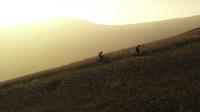 two people on e-bikes riding up a hillside at sunset - carrellata video stock e b–roll