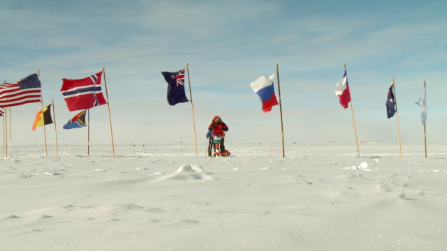 ws of two people on skis arriving at south pole marker surrounded by flags / south pole, antarctica - south pole stock videos & royalty-free footage