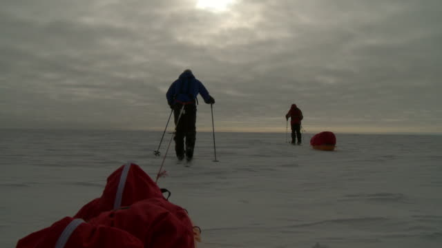 stockvideo's en b-roll-footage met ws la pov of two people on skis pulling pack sleds across ice rear view at dusk / south pole, antarctica - exploration