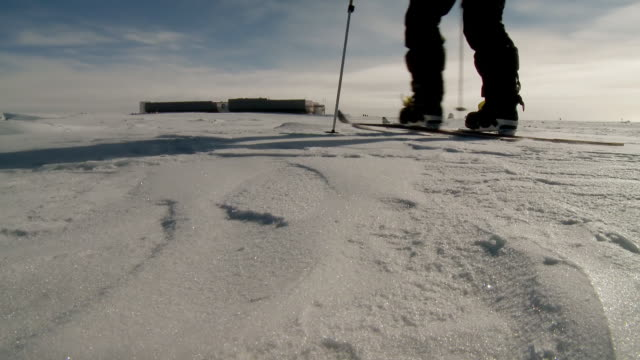 ms la of two people on skis pulling pack sleds across south pole ice with us south pole base in distance / south pole, antarctica - antarctica people stock videos & royalty-free footage
