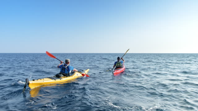 Two people paddling their kayaks across the sea in sunshine