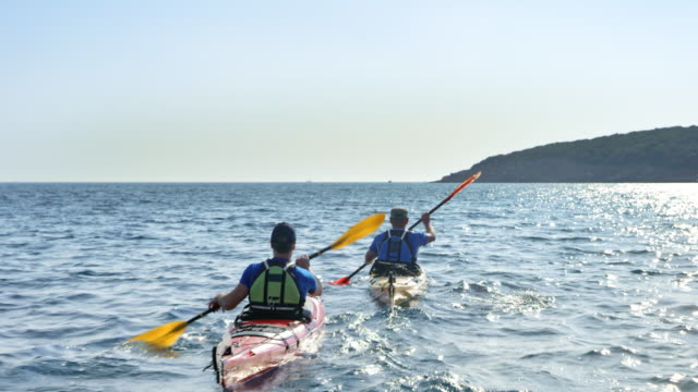 two people paddling their kayaks at sea on a sunny day - kayak stock videos & royalty-free footage