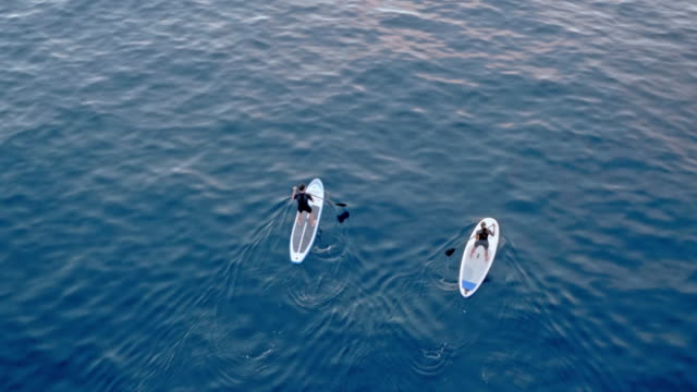 AERIAL Two people paddling their stand up paddle boards across a calm sea surface