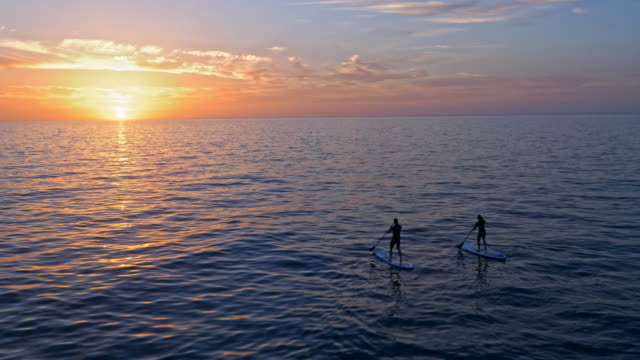 aerial two people paddling their sups in beautiful sunset over the adriatic sea - orizzonte sull'acqua video stock e b–roll