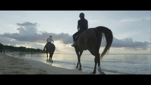 two people riding along a beach on horseback - horseback riding stock videos & royalty-free footage