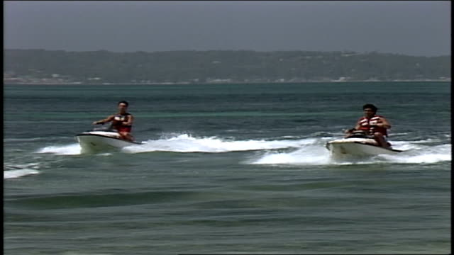 vidéos et rushes de two people riding jet skis to shore in jamaica - 1980 1989