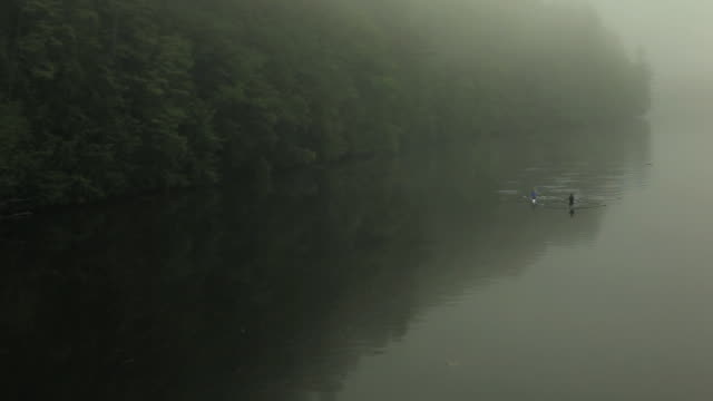 ha ws two people rowing past in single sculls on the connecticut river at dawn/ hanover, new hampshire, usa - 隣り合わせ点の映像素材/bロール