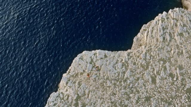 stockvideo's en b-roll-footage met luchtfoto twee mensen lopen op een witte klif stijgen van de blauwe zee bij zonsondergang - cres kroatië