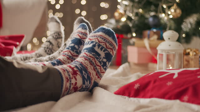 two people sit on a blanket on the floor and move their feet in christmas socks - sock stock videos & royalty-free footage