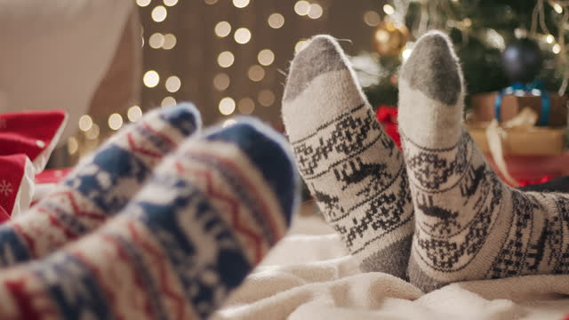 two people sit on a blanket on the floor and move their feet in christmas socks - cozy stock videos & royalty-free footage
