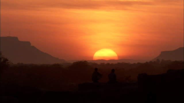 two people sit on a rocky wall and gaze at a glowing orange sun in the shibam desert. - yemen stock videos & royalty-free footage