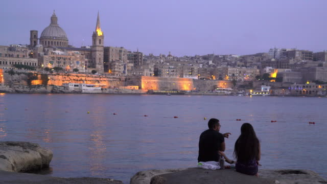 stockvideo's en b-roll-footage met two people sit on shore of valletta, malta - unesco world heritage site - valletta