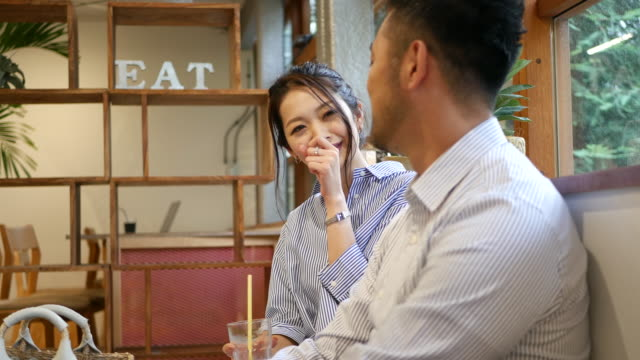 two people sitting at a cafe, having a chat - part of a series stock videos & royalty-free footage