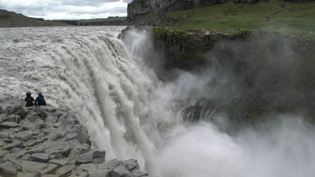 Two people sitting on the rocks nearby the mighty  Dettifoss  waterfall  in Vatnajökull National Park, Iceland  in summertime