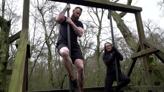 vidéos et rushes de deux personnes glisser vers le bas de mât au cours de l'agression / course d'obstacles - slow motion - poteau d'appui
