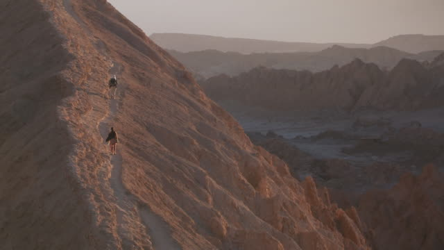 ws two people slowly climbing up on slope of  desert of valley of the moon  / san pedro de atacama, norte grande, chile - san pedro de atacama stock videos & royalty-free footage