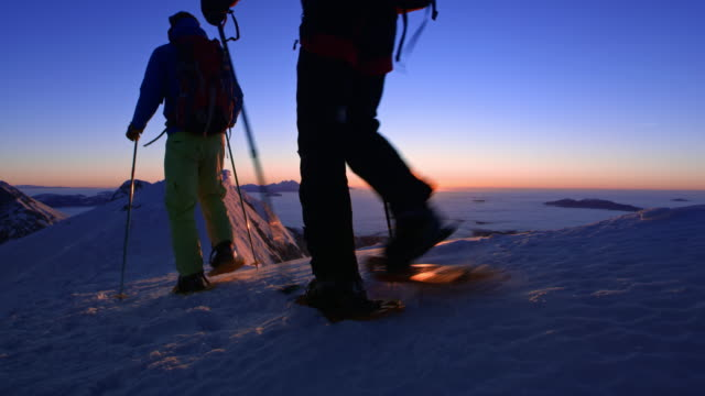 ds two people snowshoeing across a ridge into sunset - slovenia stock videos & royalty-free footage