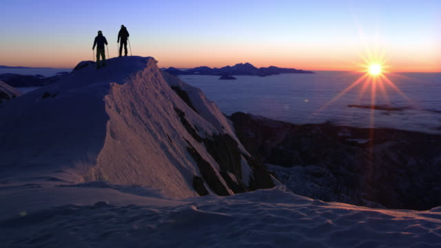 DS Two people snowshoeing over the mountain ridge at sunset