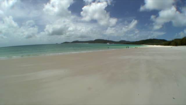 WS Two people standing by inflatable raft on beach shore, Whitsunday Islands, Queensland, Australia