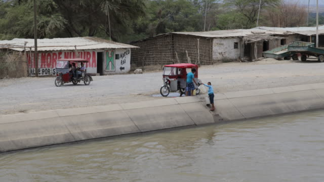 two people stopped their rickshaw vehicle at a river to fill up buckets with water in sullana peru - rickshaw stock videos and b-roll footage