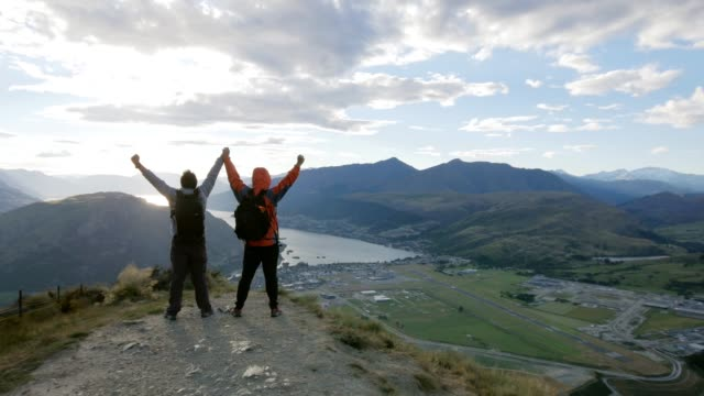 Two people summited on the top of Mountain peak with sunset time