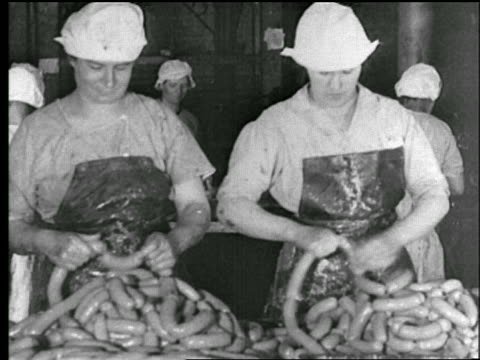 b/w 1922 two people twisting sausages to make links in factory / chicago / newsreel - sausage stock videos & royalty-free footage