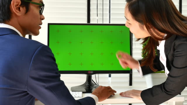 Two people using at the computer with green screen