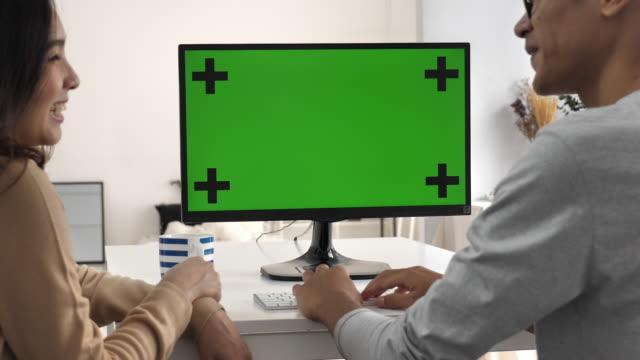 Zwei Personen mit Computer und im Gespräch mit Greenscreen, Chroma-key