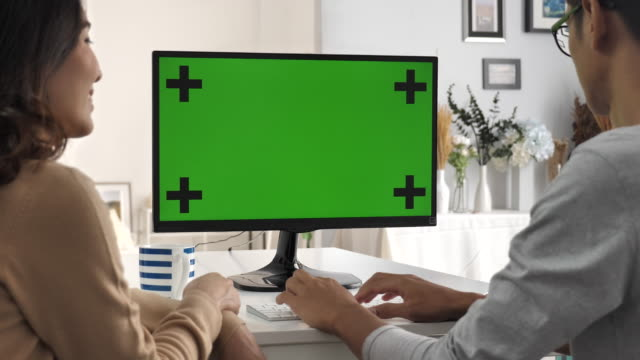 Two people using Computer and talking to green screen, Chroma key