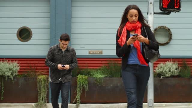 vídeos de stock, filmes e b-roll de ms two people using iphones crossing street / santa monica, california, united states - 2012