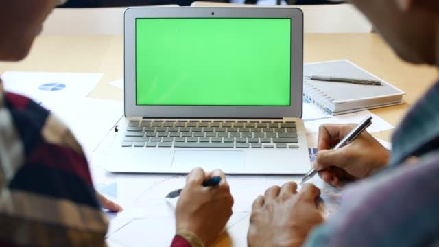 vidéos et rushes de deux personnes à l'aide d'écran d'ordinateur portable vert - équipement