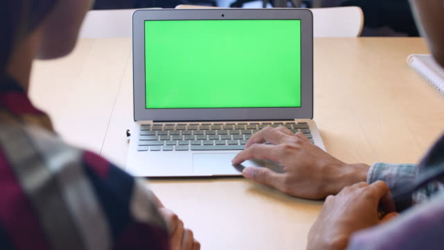 vídeos de stock e filmes b-roll de two people using laptop with green screen, chroma key - sobre os ombros vista traseira