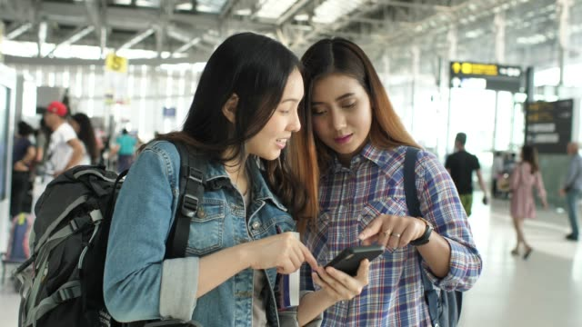 two people using phone at airport