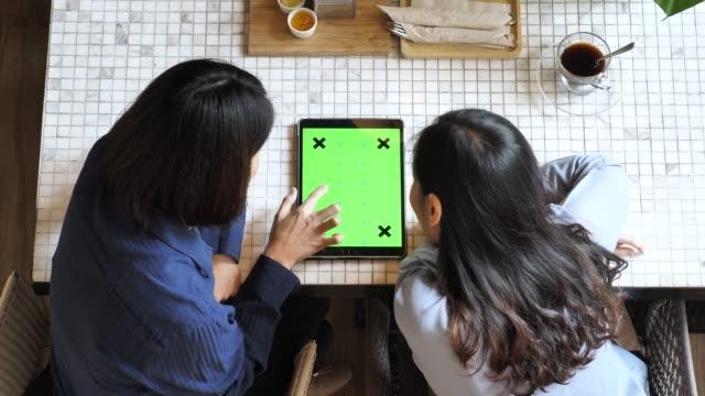 stockvideo's en b-roll-footage met twee mensen met behulp van tablet pc groen scherm, hoge hoekmening - over shoulder