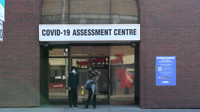 two people waiting outside a covid-19 assessment center in bathurst street on april 4, 2021 in toronto, ontario, canada - two people stock videos & royalty-free footage