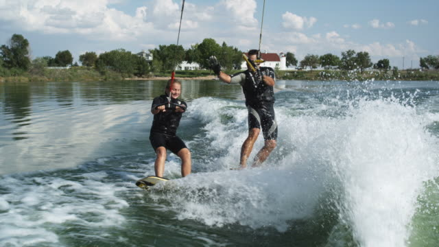 two people wakeboarding behind a boat