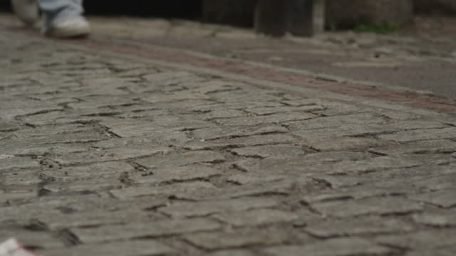 two people walk in lockstep on an uneven brick road. - uneven stock videos & royalty-free footage