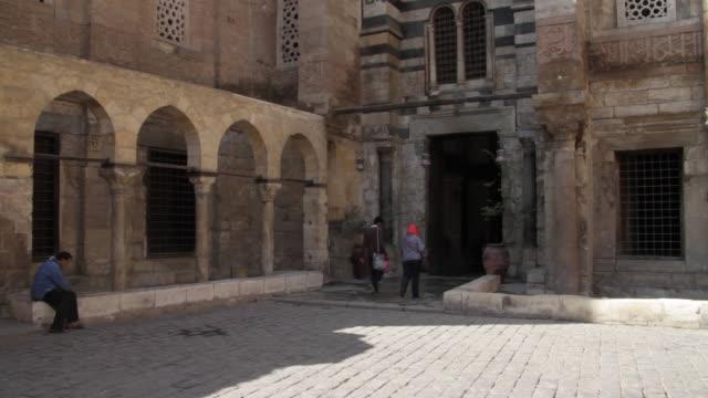 stockvideo's en b-roll-footage met two people walk into stone building in coptic cairo. - plaatselijk monument