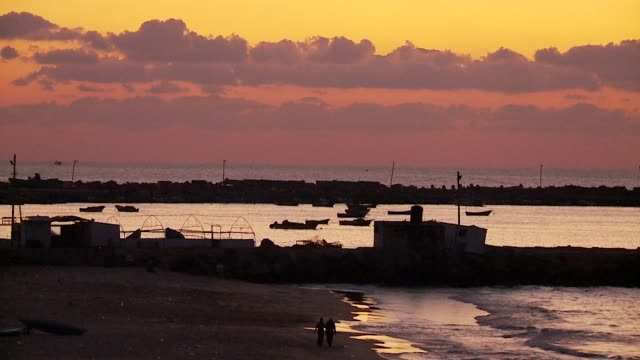 two people walk on beach at sunset - gaza city stock videos & royalty-free footage