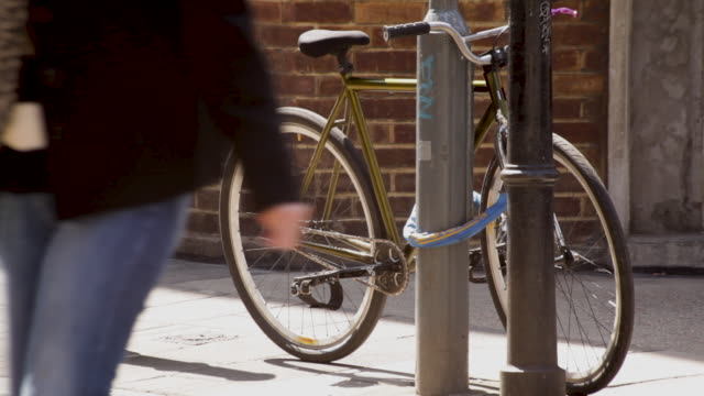 Two people walk past a golden-coloured bicycle locked to a lamppost in East London, UK.