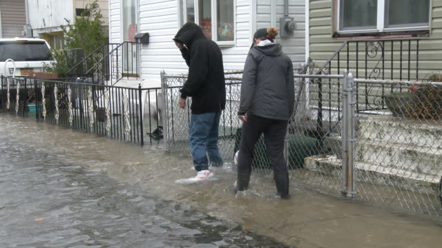 Two people walk through storm surge flooding on a residential street during a powerful nor'easter in the town of Broad Channel New York