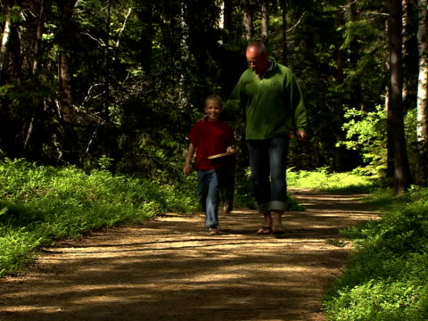 Two people walking in the forest carrying casting rod and fishing tackle Sweden.