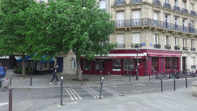 two people with protective masks and one person riding a bike on the street bar and restaurant closed corner quai d'orléans and rue jean du bellay... - three people stock videos & royalty-free footage