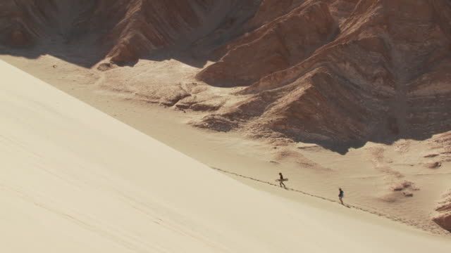 ws pan two people with sandboarder sand walking slowly up through valley far below / san pedro de atacama, norte grande, chile   - newoutdoors stock videos & royalty-free footage