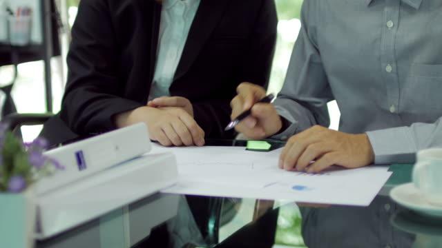 vídeos y material grabado en eventos de stock de dos personas de trabajo y reunión en la oficina con el documento gráfico para la presentación de dolly tiro de izquierda a derecha - accesibilidad