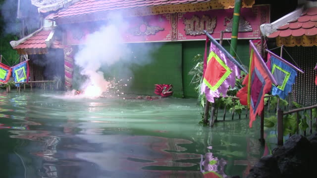 ws two person playing with firework in water wearing dragon costume, building in background / ho chi minh city, thailand - vietnam stock videos & royalty-free footage
