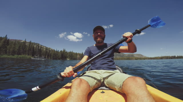 pov of two persons kayaking in a calm lake - rowing boat stock videos & royalty-free footage
