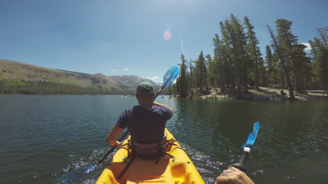pov of two persons kayaking in a calm lake - canoeing stock videos and b-roll footage