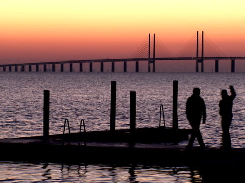 Two persons walking on a jetty in front of Oresundsbron Malmo Sweden.